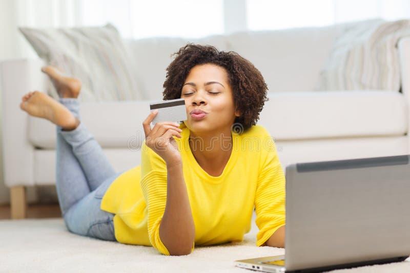 Lycklig afrikansk kvinna med bärbara datorn och kreditkorten arkivbild