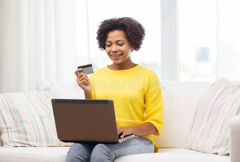 Lycklig afrikansk kvinna med bärbara datorn och kreditkorten royaltyfria bilder