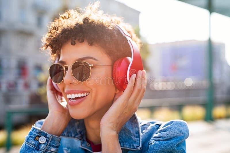 Lycklig afrikansk kvinna med hörlurar royaltyfri fotografi
