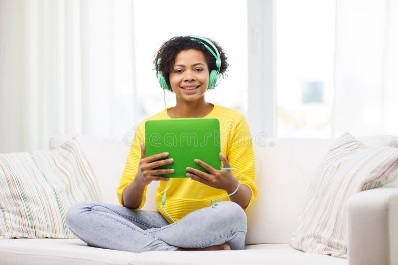 Lycklig afrikansk kvinna med minnestavlaPC och hörlurar arkivfoto