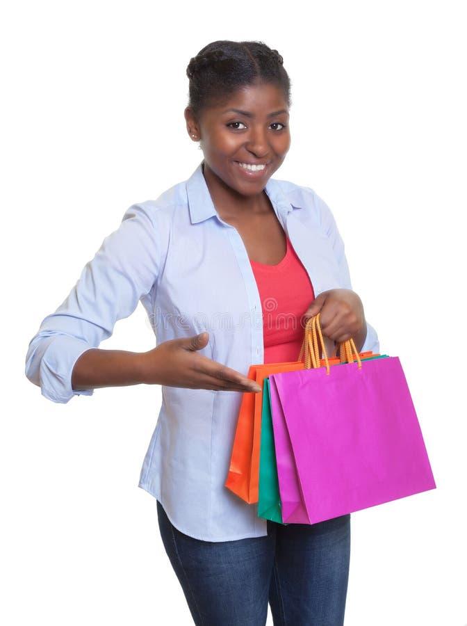 Lycklig afrikansk kvinna som framlägger hennes shoppingpåsar royaltyfria foton