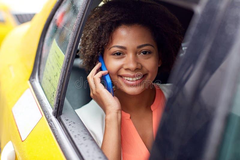 Lycklig afrikansk kvinna som kallar på smartphonen i taxi arkivbilder
