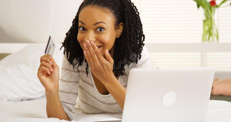 Lycklig afrikansk kvinna som ler med bärbara datorn och kreditkorten arkivfoton