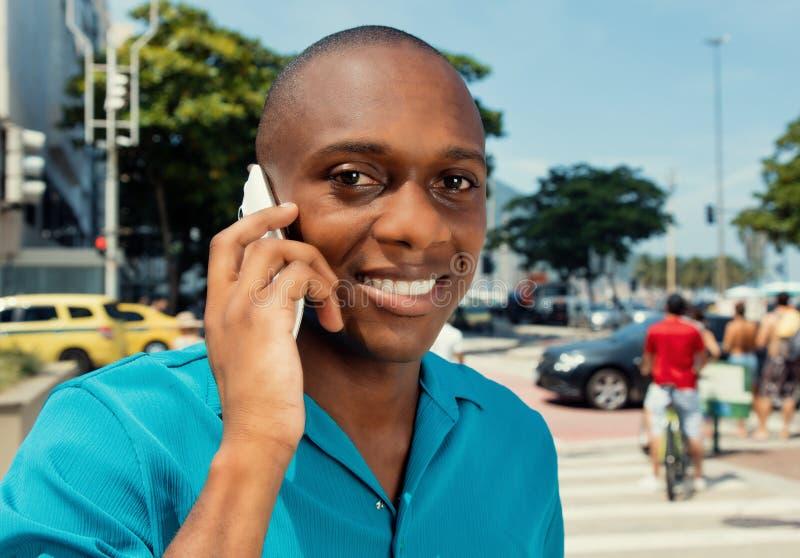 Lycklig afrikansk man som använder cell- utomhus- i en varm bioblick royaltyfri fotografi