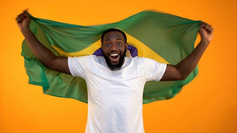 Lycklig Afro--amerikan man som rymmer den brasilianska flaggan, sp?nnande av fotbollsmatchen royaltyfri foto