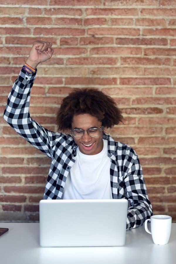 Lycklig afro--amerikan ung man som firar framgång, medan arbeta med bärbara datorn hemma arkivfoto