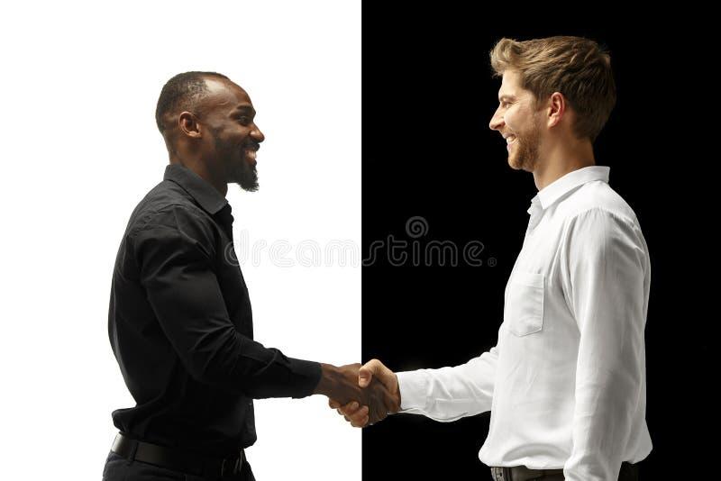 Lycklig afro för framgång och caucasian män Blandat koppla ihop Mänskligt ansikts- sinnesrörelsebegrepp royaltyfri fotografi