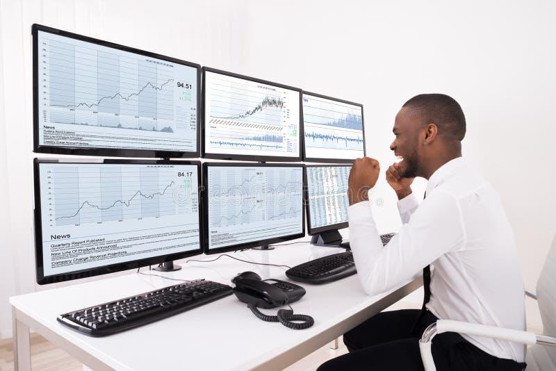 Lycklig aktiemarknadmäklare Looking At Graphs på den åtskilliga datoren royaltyfria foton