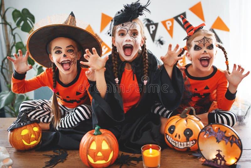 Lycklig allhelgonaafton! en grupp av barn i dräkter och med pumpor royaltyfri fotografi