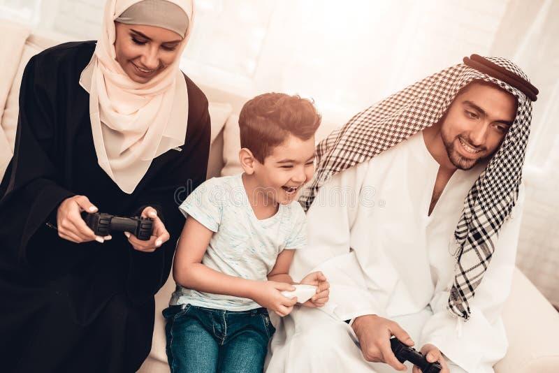 Lycklig arabisk familj som hemma spelar på konsolen royaltyfri bild
