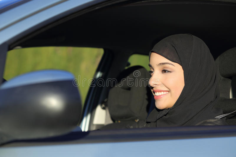 Lycklig arabisk saudierkvinna som kör en bil fotografering för bildbyråer