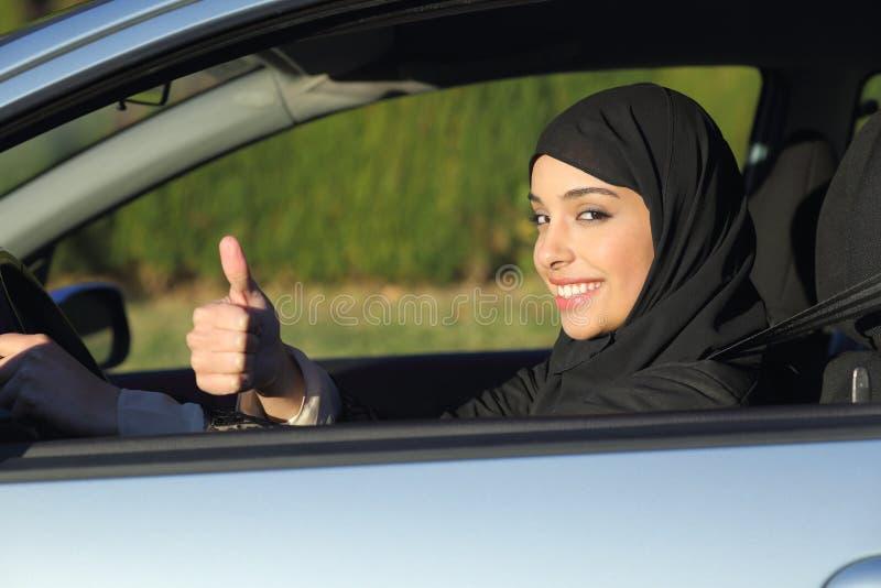 Lycklig arabisk saudierkvinna som kör en bil med tummen upp royaltyfri bild
