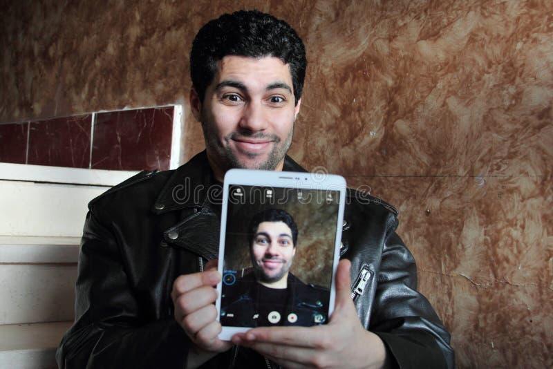 Lycklig arabisk ung affärsman i omslaget som tar selfie royaltyfria bilder