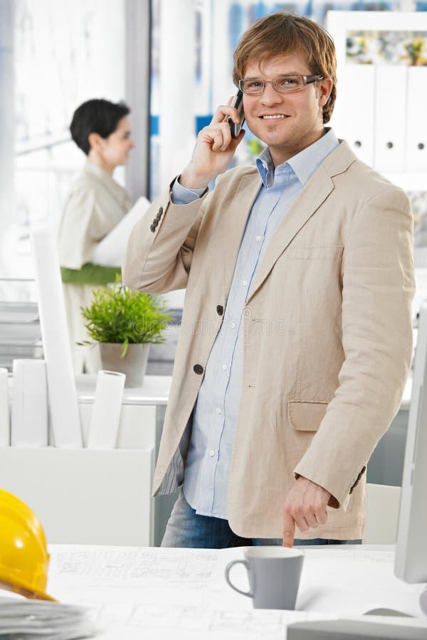 Lycklig arkitekt på kontoret som talar på mobiltelefonen royaltyfri bild