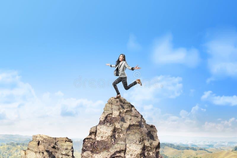 Lycklig asiatisk affärskvinna som överst hoppar av berget arkivbild