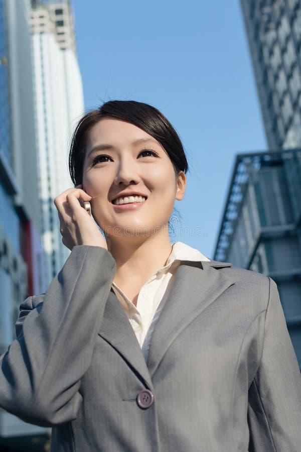 Lycklig asiatisk affärskvinna som talar på telefonen och går på stree arkivbilder