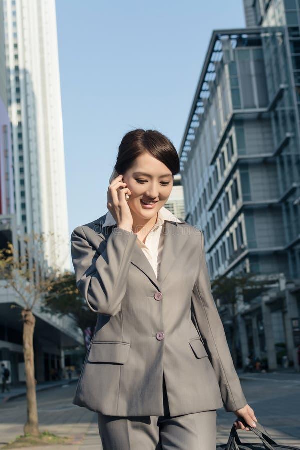 Lycklig asiatisk affärskvinna som talar på telefonen och går på stree arkivfoton