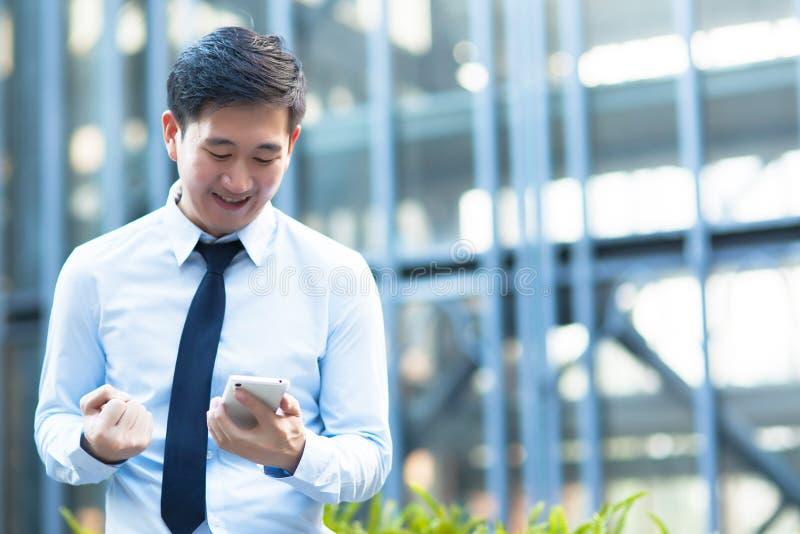 Lycklig asiatisk affärsman som mottar goda nyheter royaltyfri bild