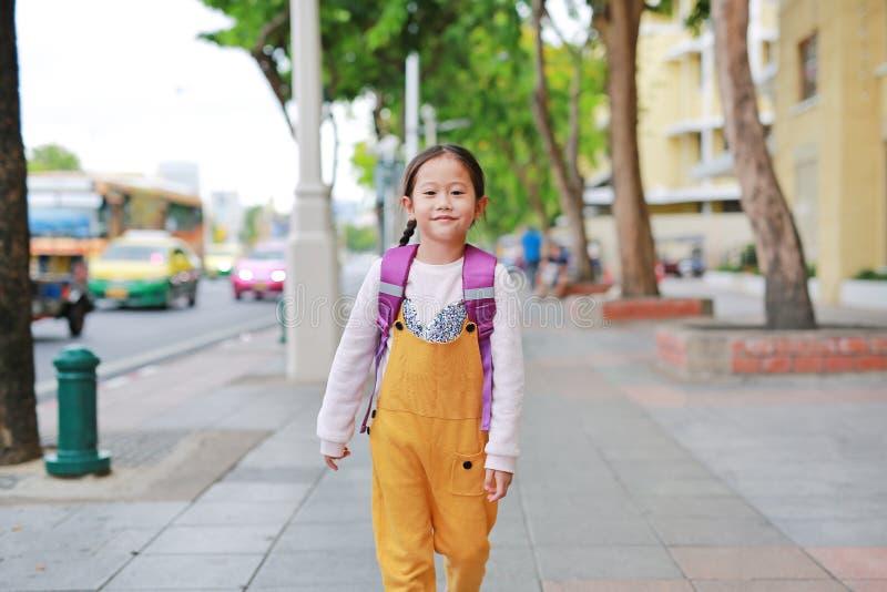 Lycklig asiatisk barnflicka som går med studentskuldraskolväskan Liten skolflicka med en främre sikt för ryggsäck tillbaka skola  royaltyfria foton