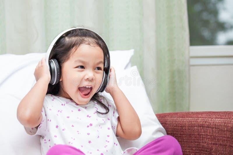 Lycklig asiatisk barnflicka som har gyckel som lyssnar musiken arkivbilder