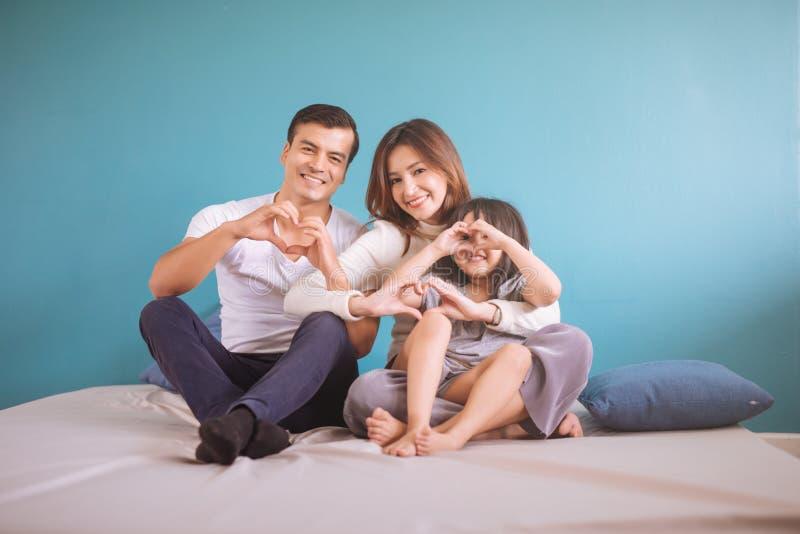Lycklig asiatisk familj för stående som gör hjärtaform i sovrum fotografering för bildbyråer