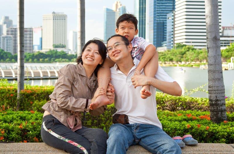 Lycklig asiatisk familj i stadsträdgård royaltyfria foton