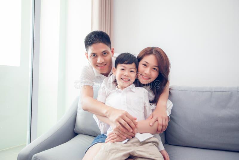 Lycklig asiatisk familj med sonen som ?r hemmastadd p? soffan som spelar och skrattar royaltyfri fotografi