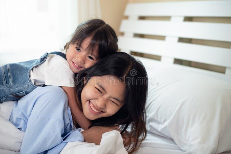 Lycklig asiatisk familj som älskar barn, ungen och hennes syster som tillsammans kopplar av i säng arkivbilder