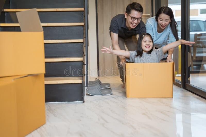 Lycklig asiatisk familj som flyttar sig till det nya huset med kartonger royaltyfri fotografi