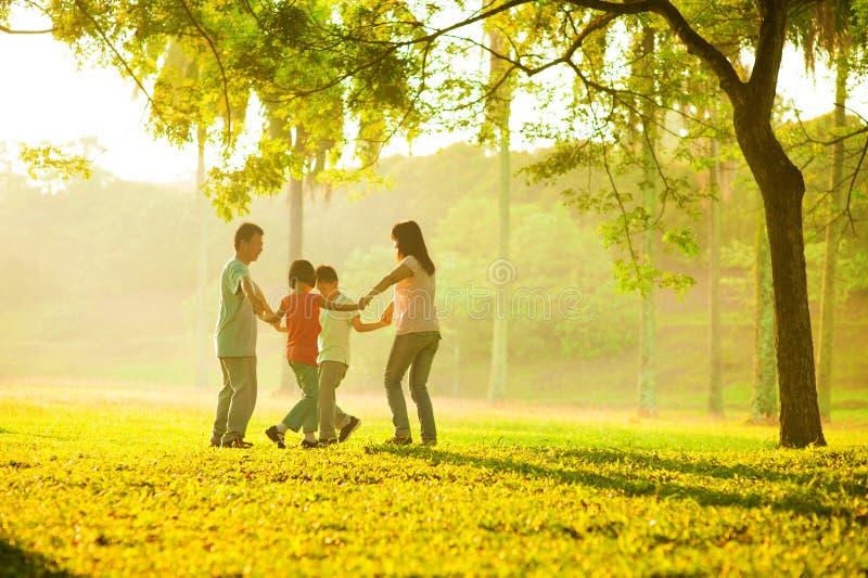 Lycklig asiatisk familj som leker på sätta in royaltyfri fotografi