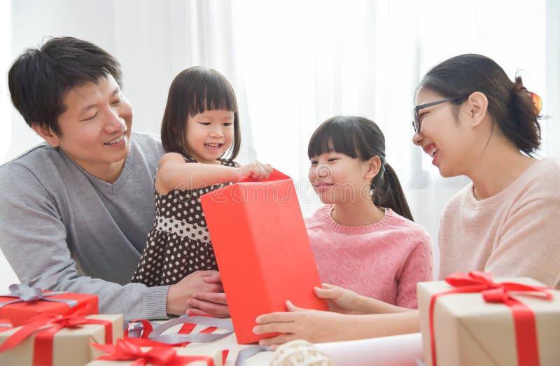 Lycklig asiatisk familj som packar upp en gåvaask royaltyfri foto