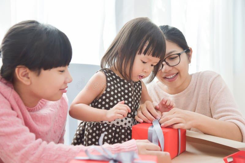 Lycklig asiatisk familj som slår in en gåvaask royaltyfri bild