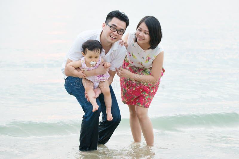 Lycklig asiatisk familj som spelar på den utomhus- sandstranden royaltyfri foto