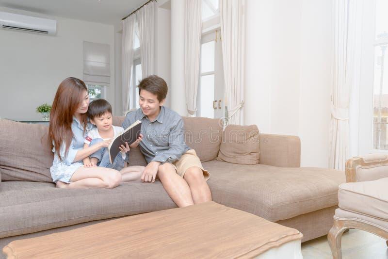 Lycklig asiatisk familjläsningsagobok hemma royaltyfria bilder