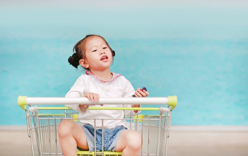 Lycklig asiatisk flicka f?r litet barn som sitter i sp?rvagnen under familjshopping i marknaden royaltyfri foto
