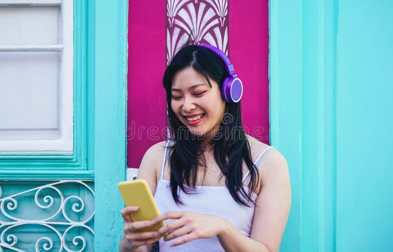 Lycklig asiatisk flicka som lyssnar till musik med utomhus- hörlurar - ung kinesisk kvinna som spelar hennes favorit- playlistmus royaltyfri fotografi