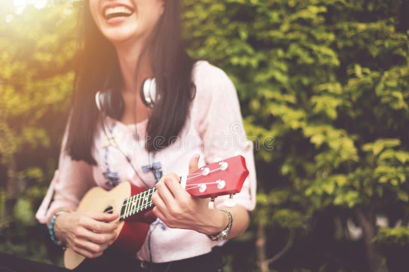 Lycklig asiatisk flicka som spelar ukulelet på utomhus- arkivfoton
