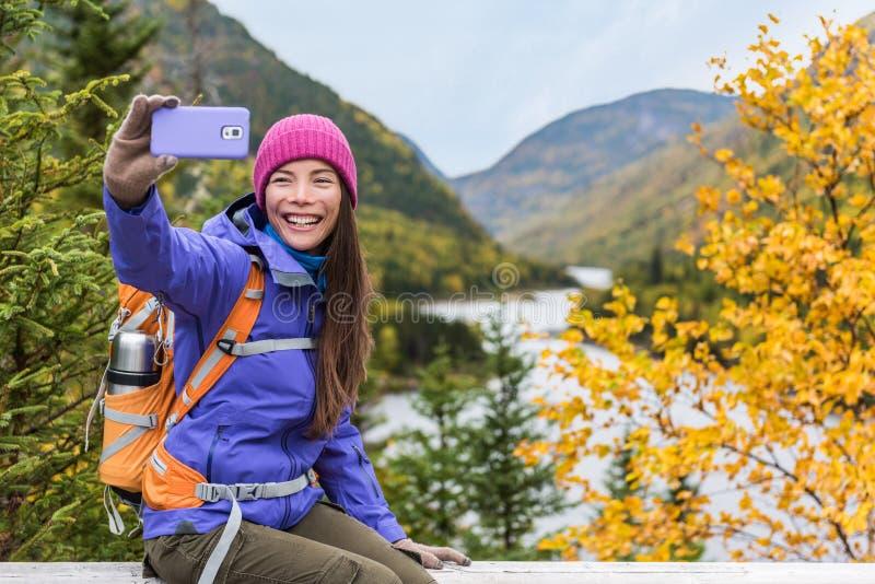 Lycklig asiatisk fotvandrarekvinna som utomhus tar smartphoneselfie på den sceniska synvinkeln i landskap för naturnedgångberg Fl royaltyfri fotografi