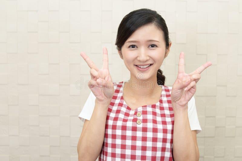 Lycklig asiatisk hemmafru arkivbild