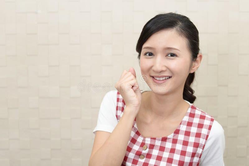 Lycklig asiatisk hemmafru royaltyfria foton