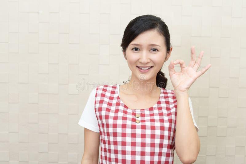 Lycklig asiatisk hemmafru arkivfoto