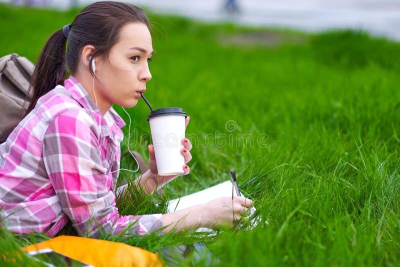 Lycklig asiatisk hipsterkvinna som ligger på gräs, ler och rymmer en kopp kaffe på äng arkivbild
