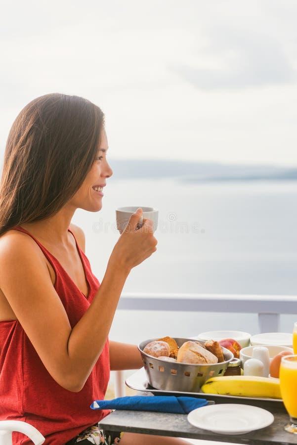 Lycklig asiatisk kvinna för kaffedrink som dricker tekoppen på morgonfrukosten utanför i solen som tycker om mat på hotellrestaur royaltyfri foto