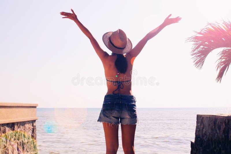 Lycklig asiatisk kvinna i bikiniöverkant och kortslutningar på stranden sommar för snäckskal för sand för bakgrundsbegreppsram royaltyfri fotografi