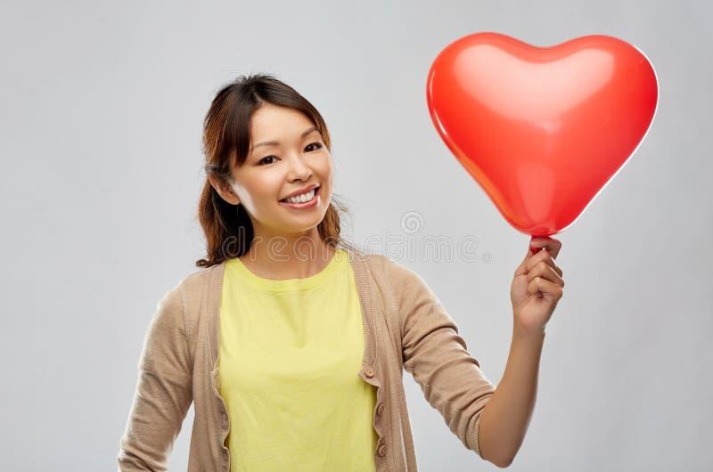 Lycklig asiatisk kvinna med den röd hjärta formade ballongen royaltyfria bilder