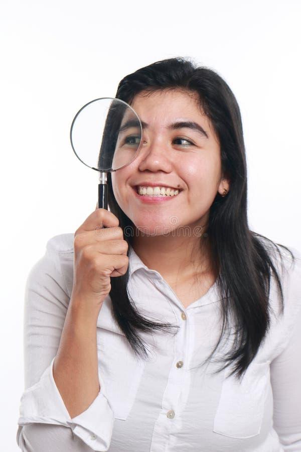 Lycklig asiatisk kvinna med förstoringsglaset royaltyfria bilder