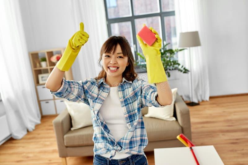 Lycklig asiatisk kvinna med svampen som hemma g?r ren royaltyfri foto