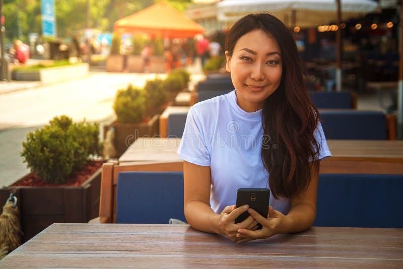 Lycklig asiatisk kvinna som använder den smarta telefonen, medan sitta i kafé royaltyfri bild