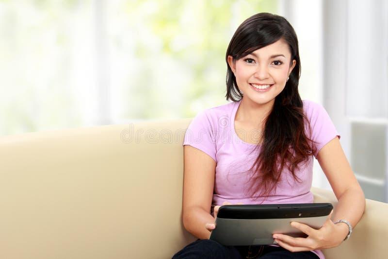 Lycklig asiatisk kvinna som använder tabletPC royaltyfri bild