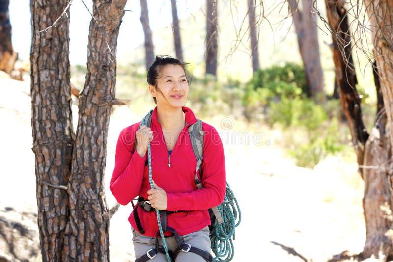 Lycklig asiatisk kvinna som fotvandrar i skogen royaltyfri foto